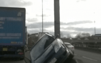 Woman's car ends up on its side against concrete barrier after crash
